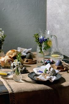 Nakrycie stołu wielkanocnego z kolorowymi i czekoladowymi jajkami, bułeczki z krzyżem na gorąco, bukiet kwiatów, pusty talerz ceramiczny z serwetką, szklanka napoju lemoniadowego na drewnianym stole z tekstylnym obrusem