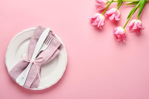 Nakrycie stołu wielkanocnego z kwiatowym wystrojem na różowym stole. elegancka kolacja. makieta. widok z góry.