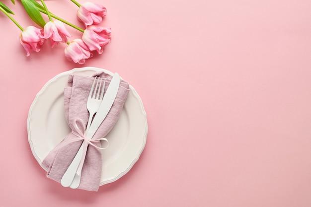 Nakrycie stołu wielkanocnego z kwiatowym wystrojem na różowym stole