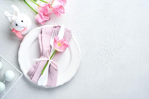 Nakrycie stołu wielkanocnego z kwiatowym wystrojem na szarym stole. elegancka kolacja. makieta. widok z góry.