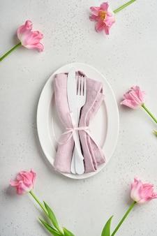 Nakrycie stołu wielkanocnego z kwiatowym wystrojem na szarym stole