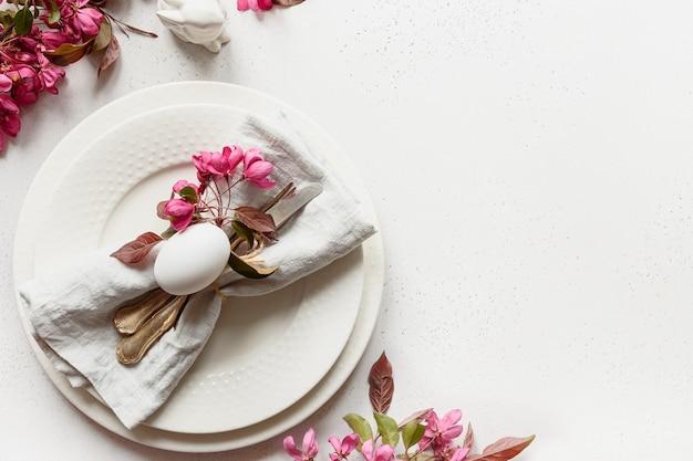 Nakrycie stołu wielkanocnego z kwitnącymi kwiatami jabłoni na białym stole.