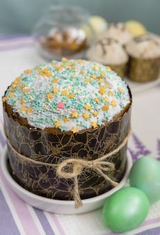 Nakrycie stołu wielkanocnego z tradycyjnym ciastem, kolorowymi jajkami i obrusem