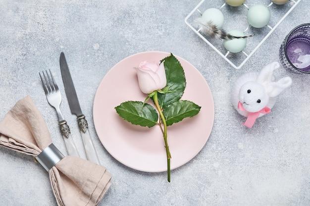 Nakrycie stołu wielkanocnego ze świeżą różową różą na szarym kamiennym stole. widok z góry. elegancja świąteczna kolacja wielkanocna.