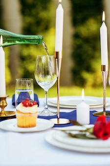 Nakrycie stołu, wino przelewa się z butelki do kieliszka, świece i kwiat na zbliżenie talerzu, nikt. luksusowe sztućce i biały obrus, zastawa stołowa na zewnątrz