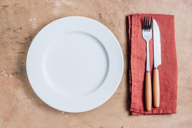 Nakrycie stołu z białym talerzem, widelcem, nożem i serwetkami na rustykalnym stole.