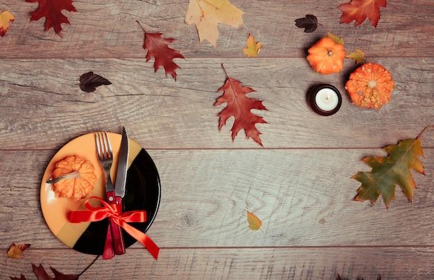 Nakrycie stołu z jesiennym wystrojem. widelec, nóż, serwetka, sztućce, kolorowe listki. dekoracje świąteczne. kolacja z okazji święta dziękczynienia. jesienny nastrój, halloween, święto dziękczynienia, koncepcja wakacje. widok z góry