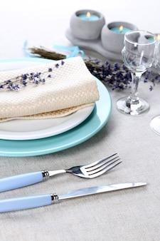 Nakrycie stołu z lawendowymi kwiatami na jasnym tle obrusu