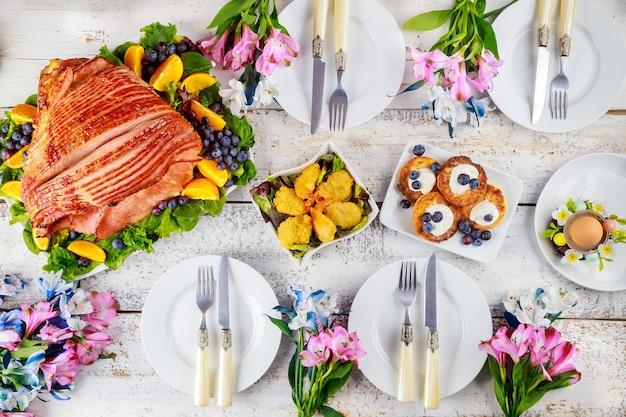 Nakrycie stołu z pieczoną szynką wieprzową na stole wielkanocnym. koncepcja wakacje.