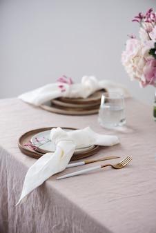 Nakrycie stołu z ręcznie robionymi ceramicznymi talerzami na lnianym obrusie i kwiatami. koncepcja imprezy