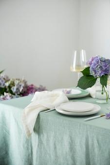 Nakrycie stołu z ręcznie robionymi ceramicznymi talerzami na zielonym lnianym obrusie i kwiatami. koncepcja imprezy