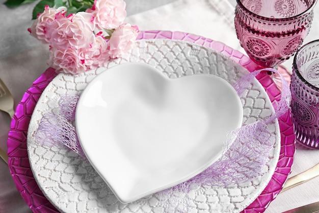 Nakrycie stołu z talerzem w kształcie serca i kwiatów, zbliżenie