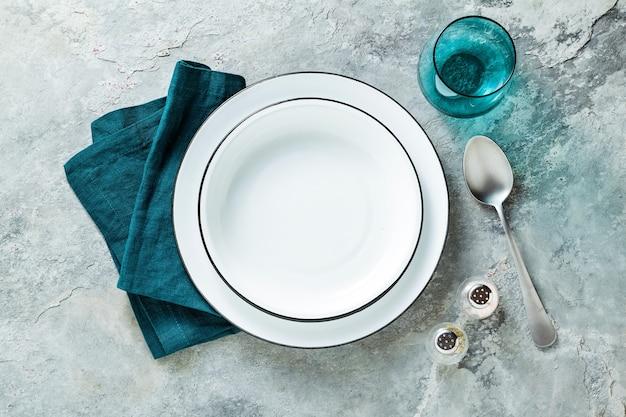Nakrycie stołu z zestawem pustych talerzy na kamiennym tle
