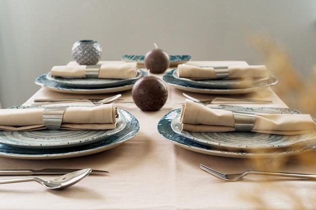 Nakrycie stołu ze stylowymi naczyniami na beżowym obrusie