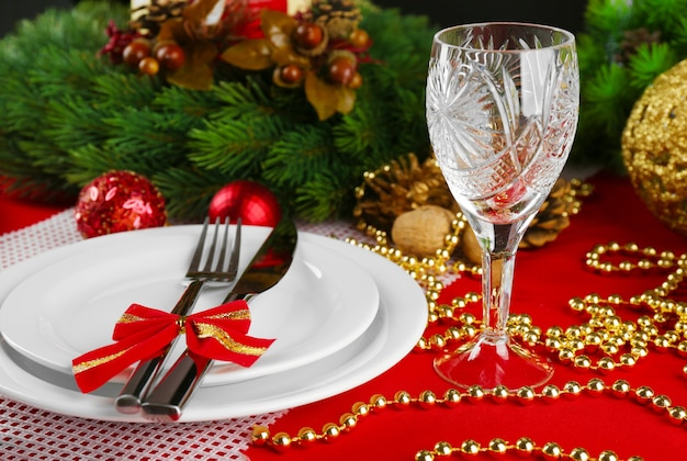 Nakrycie stołu ze świąteczną dekoracją na czerwonym obrusie