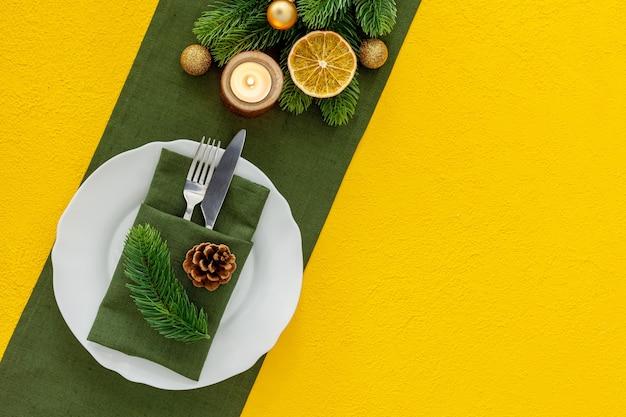 Nakrycie stołu ze świerkiem, talerz, sztućce na białym tle widok z góry