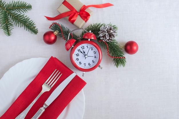 Nakrycie świąteczne z czerwonym budzikiem na białym obrusie. widok z góry. skopiuj miejsce.