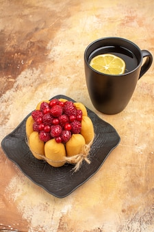Nakryj do stołu prezentowy tort i herbatę w czarnej filiżance z cytryną na stole mieszanym