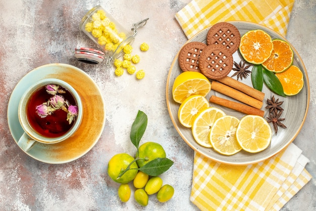 Nakryj stolik na kawę i herbatę z filiżanką herbaty i herbatnikami i plasterkami cytryny na białym stole