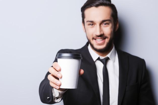 Naładuj się! portret pewny siebie młody człowiek w formalwear patrząc na kamerę i wyciągając filiżankę kawy, stojąc na szarym tle