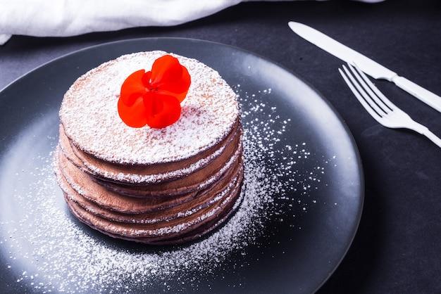 Naleśnik czekoladowy z białym proszkiem i czerwonym kwiatem na wierzchu na ciemnym naczyniu