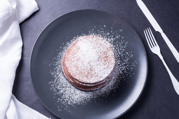 Naleśnik czekoladowy z białym proszkiem na ciemnym naczyniu
