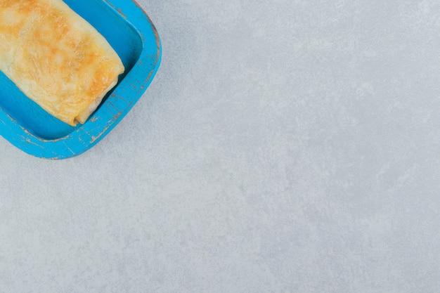Naleśnik faszerowany mięsem na niebieskim talerzu.