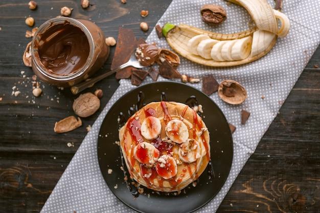 Naleśnik z pastą czekoladowo-orzechową, orzechami włoskimi i bananem na czarnym talerzu