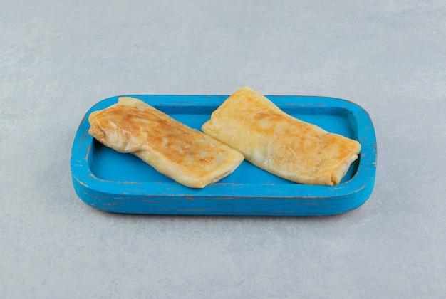 Naleśniki faszerowane mięsem na niebieskim talerzu.