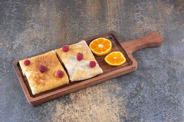 Naleśniki mleczne z jagodami i plastrami pomarańczy