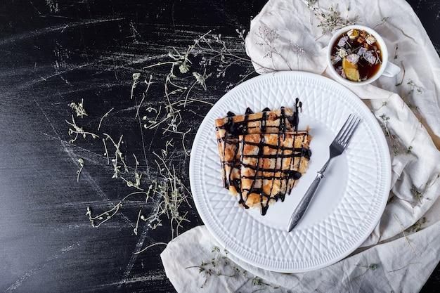 Naleśniki na białym talerzu z syropem czekoladowym i herbatą.