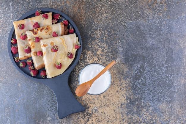 Naleśniki na czarnym półmisku z malinami i szklanką mleka