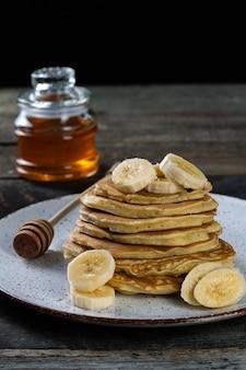Naleśniki na talerzu ceramicznym podawane z bananami i miodem na drewnianym