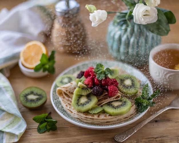 Naleśniki na talerzu z jagodami na drewnianym stole z białymi kwiatami i latającym cukrem pudrem.