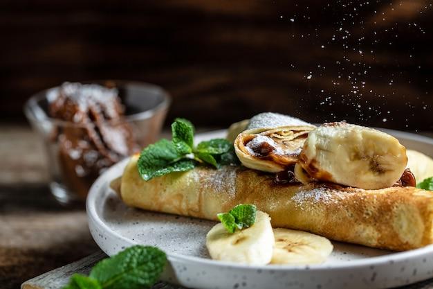 Naleśniki nadziewane kremem czekoladowym i bananem na białym talerzu