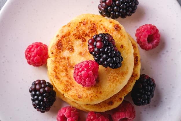 Naleśniki twarogowe, deser z ciasta twarogowego z malinami i jagodami jeżyny na talerzu