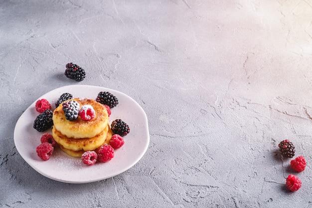 Naleśniki twarogowe i cukier puder, deser twarogowy z malinami i jeżynami na talerzu