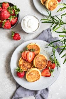 Naleśniki twarogowe lub placki z truskawkami i jogurtem naturalnym syrniki