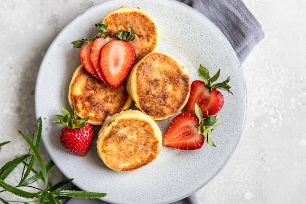 Naleśniki twarogowe lub placki z truskawkami i jogurtem naturalnym zdrowe śniadanie lub obiad