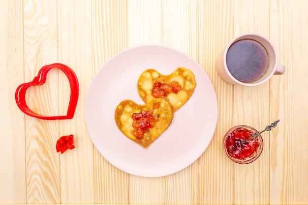 Naleśniki w kształcie serca na romantyczne śniadanie z dżemem truskawkowym i czarną herbatą