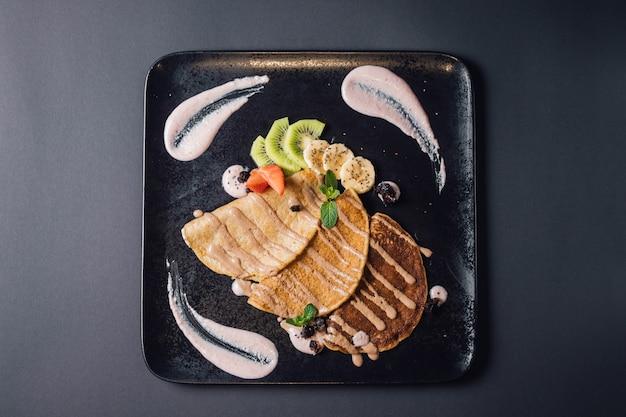 Naleśniki wegetariańskie z sezonowymi owocami i sosem tofu. zawiera mąkę pszenną, mleko roślinne, słodzone cukrem kokosowym. na talerzu, odizolowywającym na błękitnym tle