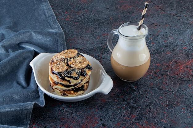 Naleśniki z bananem i czekoladą w białej misce z pyszną kawą.