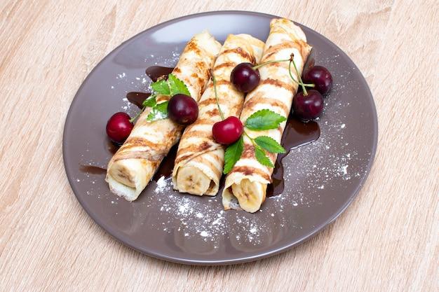 Naleśniki z bananem i truskawkami na talerzu