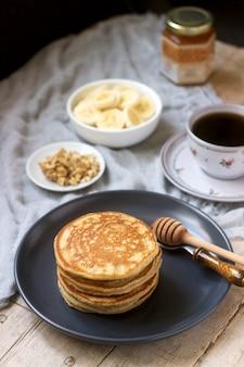 Naleśniki z bananem, orzechami i miodem, podawane z herbatą. styl rustykalny.