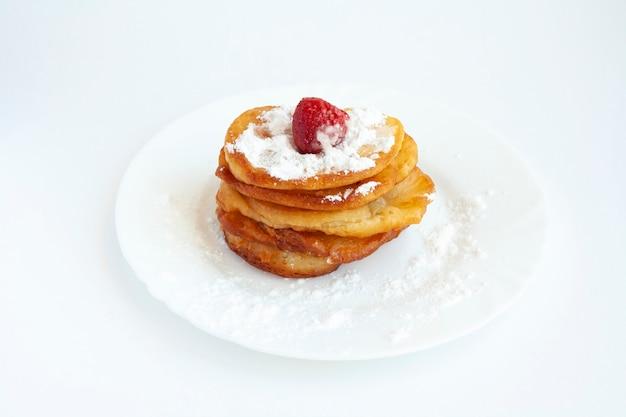 Naleśniki z cukrem pudrem i truskawkami na talerzu, na białym tle