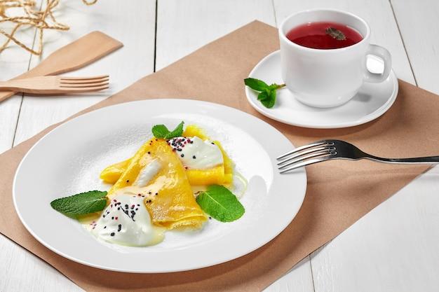 Naleśniki z cukrem pudrem ze śmietany i herbatą owocową
