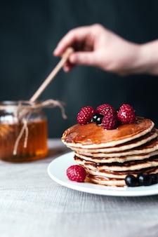 Naleśniki z jagodami i miodem na białym talerzu, ręka trzyma łyżkę w słoiku, drewniany stół.