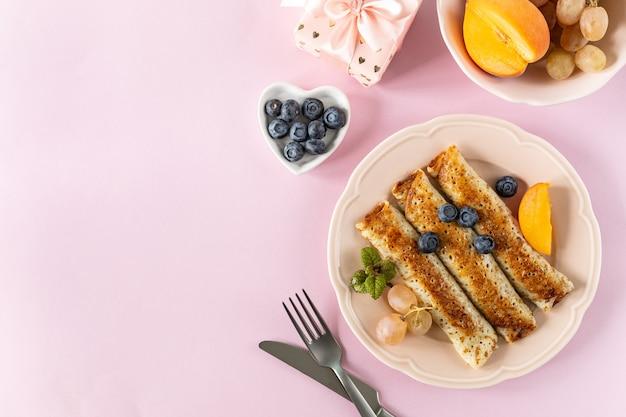 Naleśniki z jagodami i miodem na różowym pastelowym stole, widok z góry, miejsce. pyszne naleśniki, cienkie naleśniki.