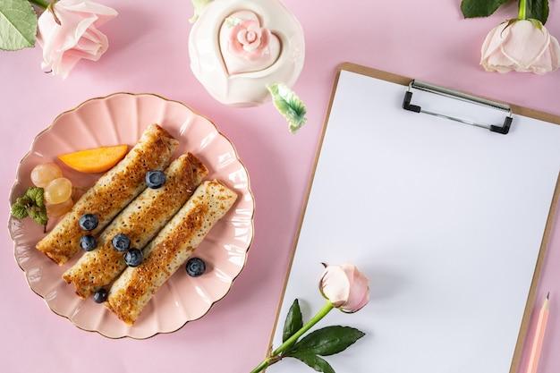 Naleśniki z jagodami i miodem na różowym pastelowym stole, widok z góry, miejsce. świąteczna piękna porcja naleśników z miejscem na tekst.