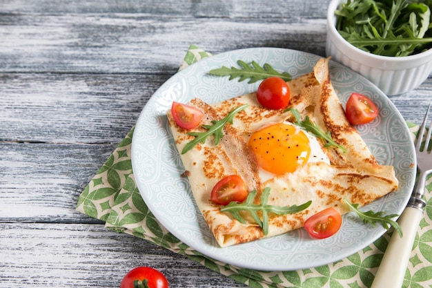 Naleśniki z jajkami, serem, liśćmi rukoli i pomidorami. galette kompletna.